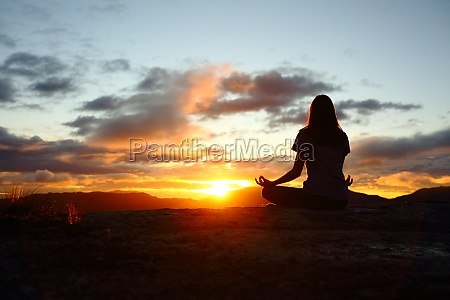 woman silhouette doing yoga at sunset