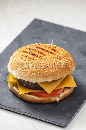 still life of cheeseburger on black