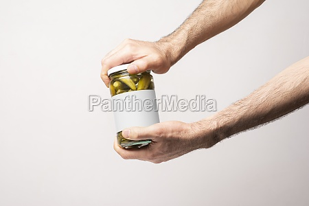 male hands opening a pickled cucumber
