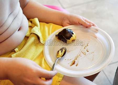 child eats a chocolate cake fat
