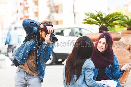 young photographer taking photographs of two