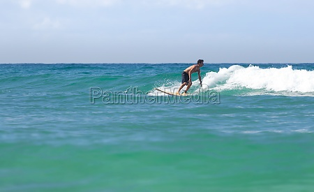 surfer on longboard rides a wave