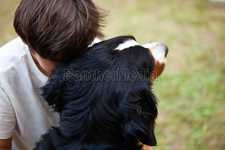 child embraces his dog resting his