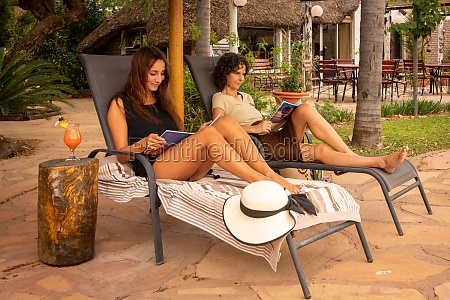 two brunettes on loungers in shade