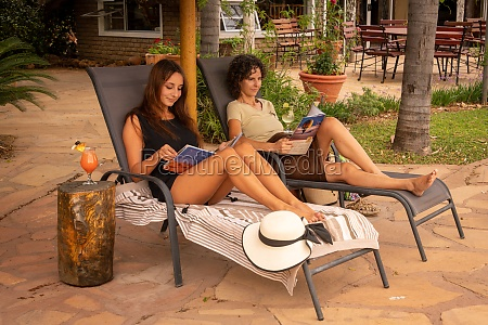 two brunettes on sun loungers in