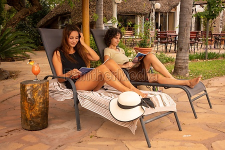 two brunettes reading on loungers in