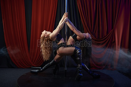 two sexy showgirls on stage striptease
