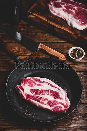 raw pork neck steak in skillet