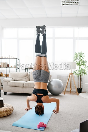 woman stands upside down online yoga