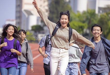happy young group students running across