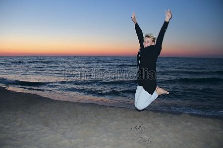 happy woman jumped on the seashore