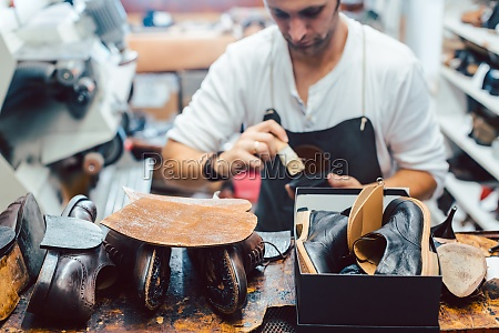 shoemaker putting glue on sole of