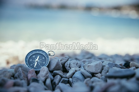 compass on the beach small stones