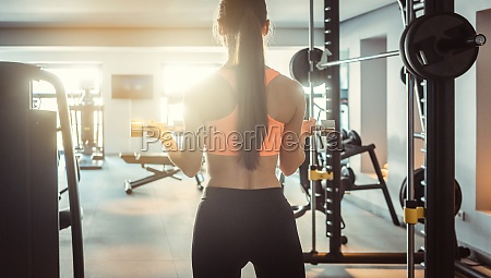 young woman lifting weights in her