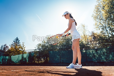 woman serving the ball in tennis