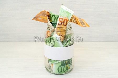 euro bills in glass jar