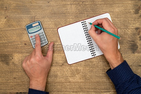 hands with calculator and notepad