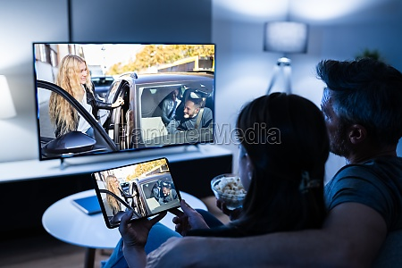 family watching tv through tablet television