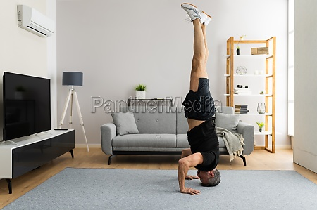 mature man doing yoga headstand exercise