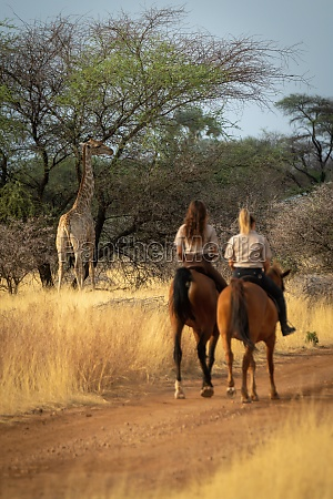 two women ride towards southern giraffe