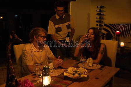 waiter shows wine to couple at