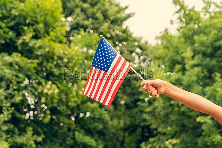 childs hand with american flag