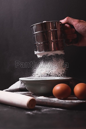 hand holds metal flour sifter a