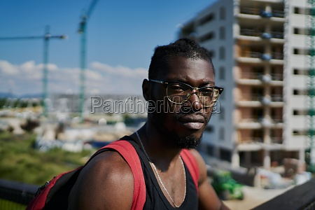 young man wearing glasses buildings in