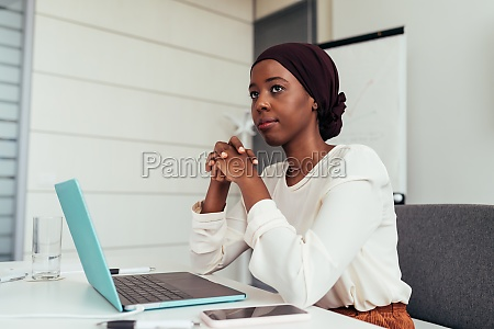 businesswoman in office with laptop thinking