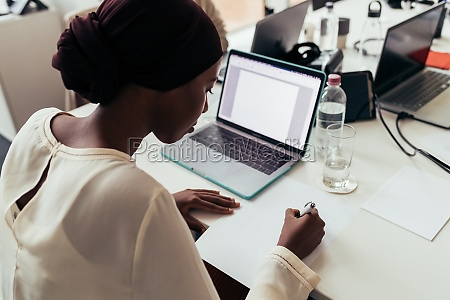 businesswoman writing notes and working on
