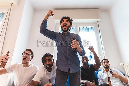 men watching sport on tv cheering