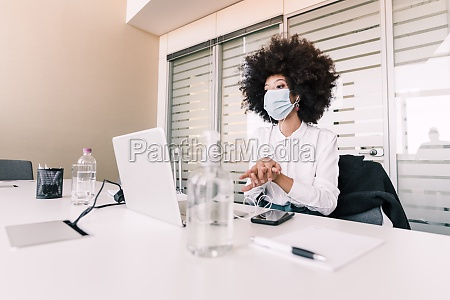 businesswoman wearing face mask and using