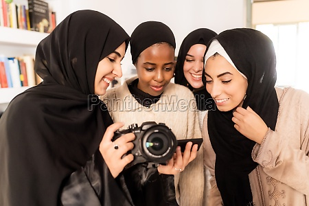 four friends looking at photographs on