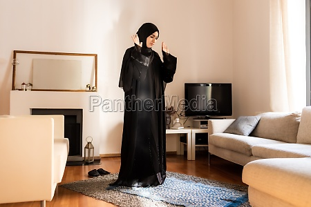 young muslim woman standing with hands