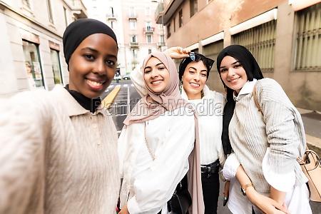 four young women wearing hijab taking