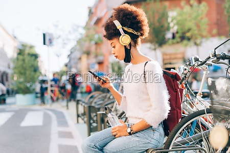 young woman outdoors looking at phone
