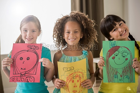 three girls holding drawings of faces