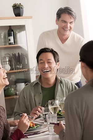 mature friends enjoying meal together