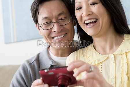 mature couple looking at digital camera