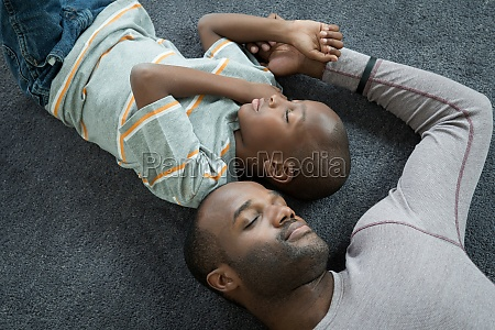 father and son lying asleep on