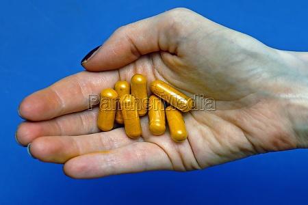 curcumin supplement pills in hand