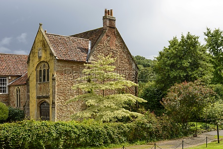 old stone cottage among trees wells