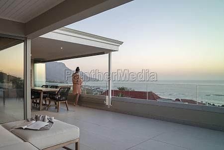 woman enjoying wine and scenic ocean
