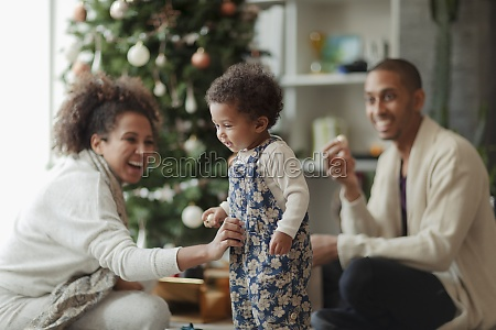 happy parents and baby daughter decorating