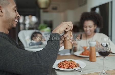 happy family enjoying spaghetti dinner at