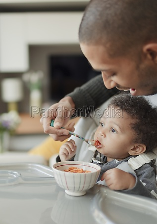 father feeding cute baby daughter at