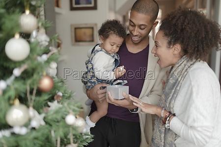happy parents helping baby daughter open