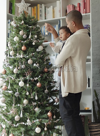 father and baby daughter decorating christmas