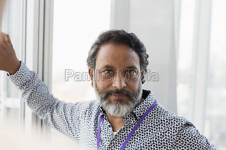 portrait confident businessman at window