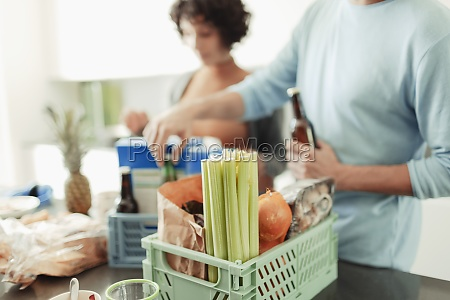 couple unloading groceries from crates at